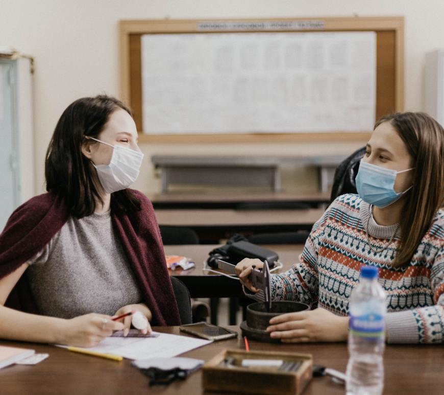 Two students talking with masks on
